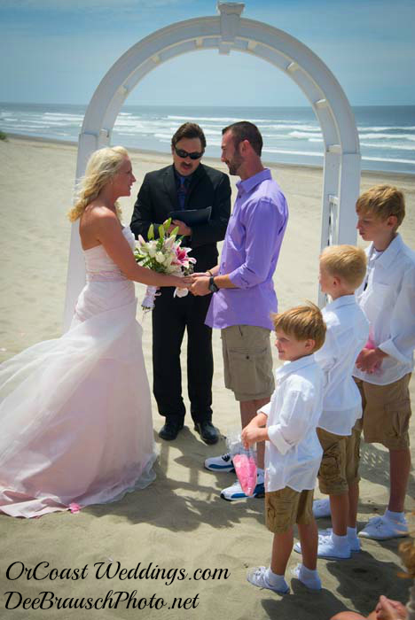 White arch on beach with Oregon coast officiant  bride groom on beach