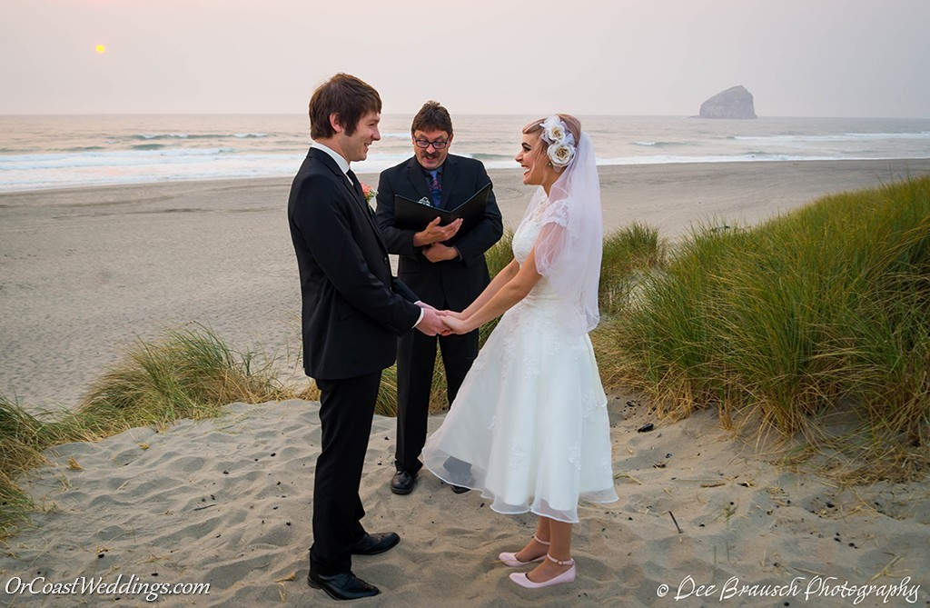 bride and groom with wedding officiant on the beach haystack rock