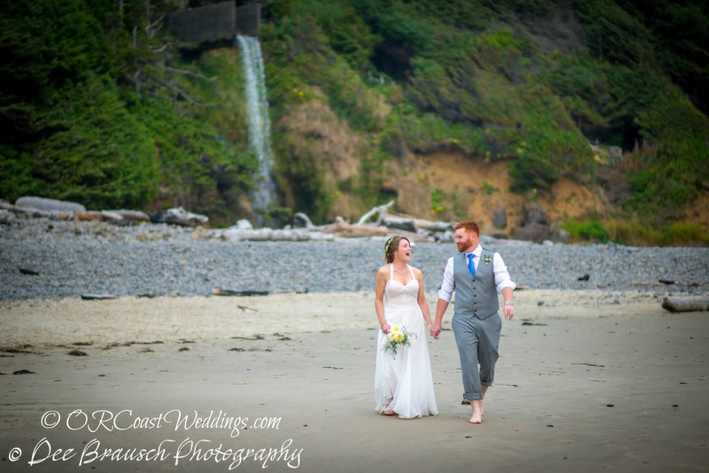 Oregon coast elopement couple on beach with waterfall